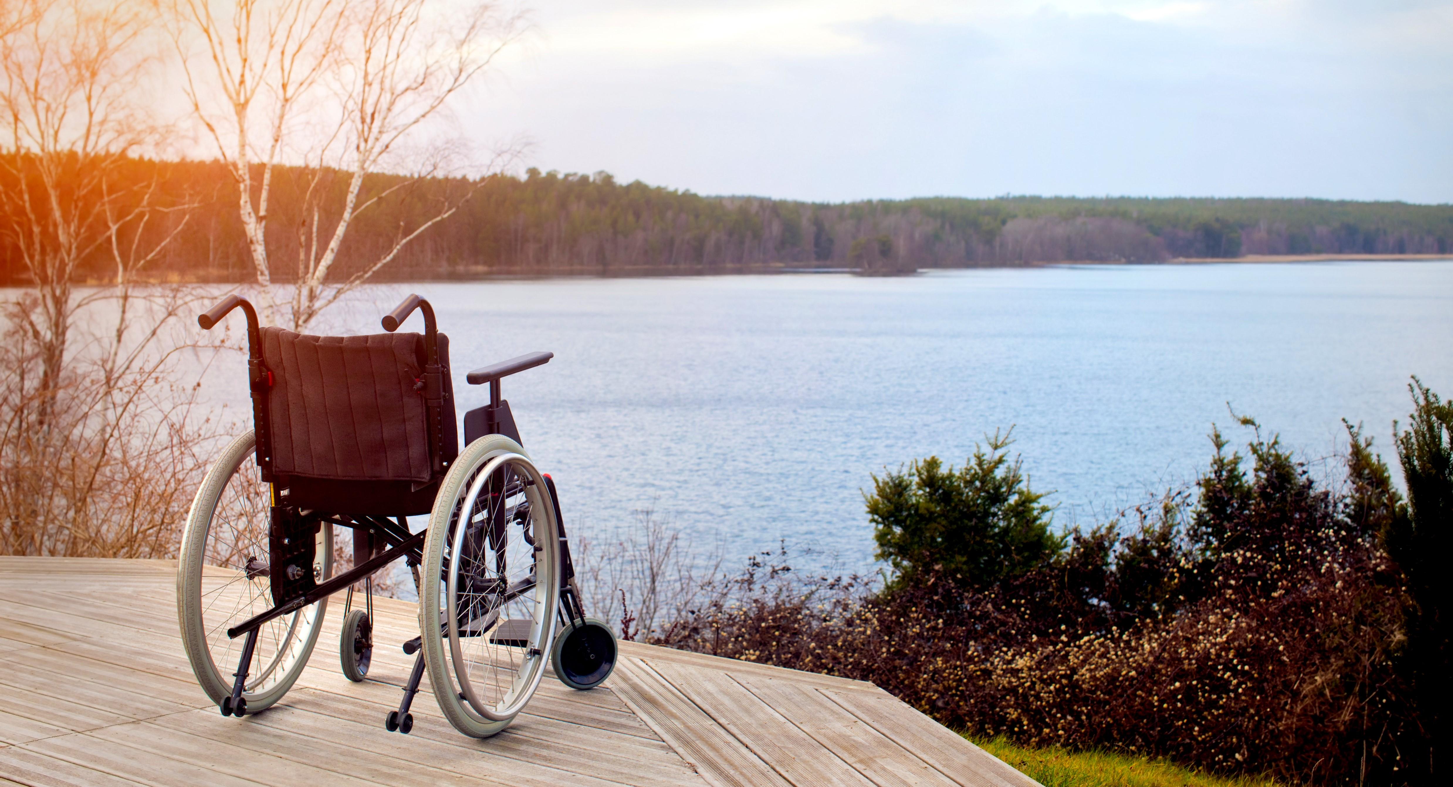 Illustrasjonsbilde erstatningsrett - Bilde av tom rullestol på en platting med utsikt over sjøen